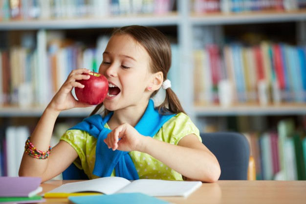 schoolgirl biting an apple in the library 1098 2597
